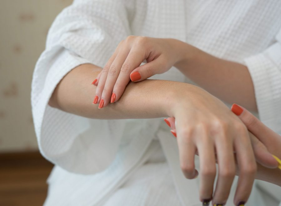 Young woman applying with finger white moisturizing cream on hand.